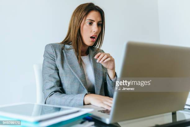 Surprised business woman looking at the laptop