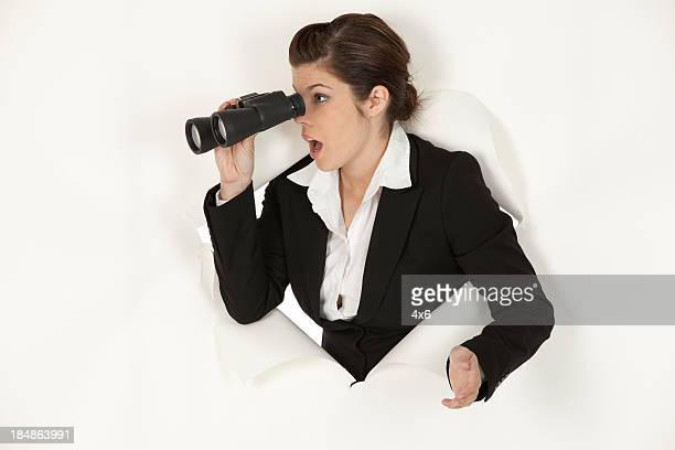 Surprised businessman emerging through a hole and using binoculars