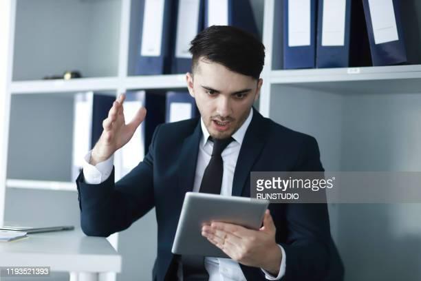 surprised businessman looking at digital tablet - 背広 ストックフォトと画像