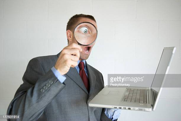 Surprised Businessman Looks at Laptop with Magnifying Glass