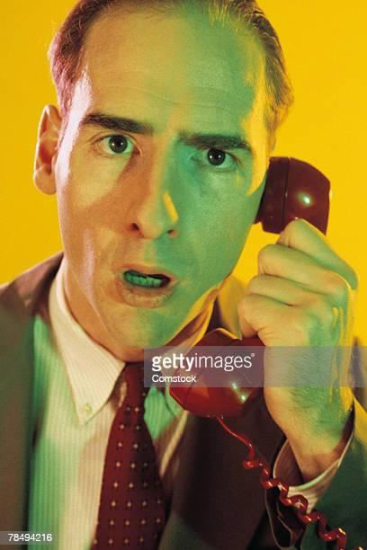 Surprised businessman talking on telephone