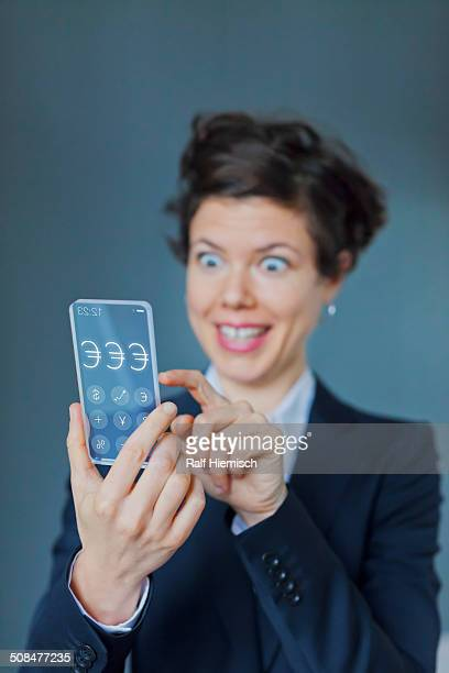 Surprised Businesswoman Using Futuristic Transparent Mobile With Euro Sign