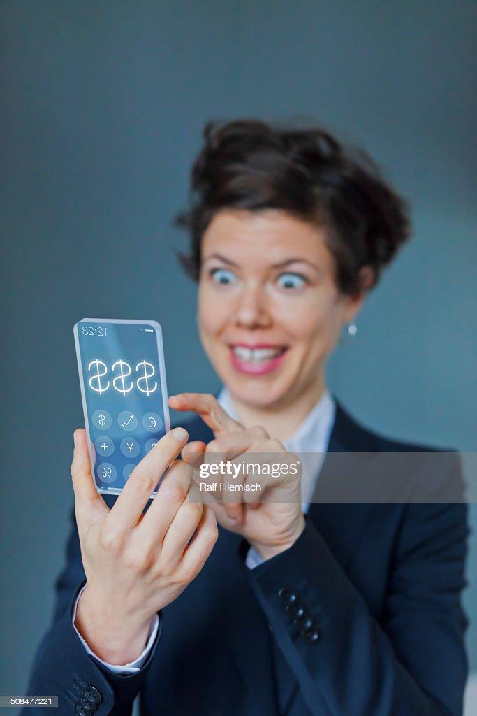 Surprised Businesswoman Using Futuristic Transparent Mobile With Dollar Sign : Stock Photo