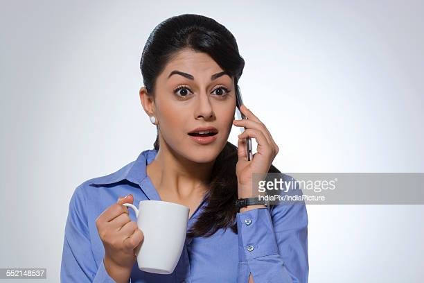 Surprised businesswoman with coffee mug using phone against gray background