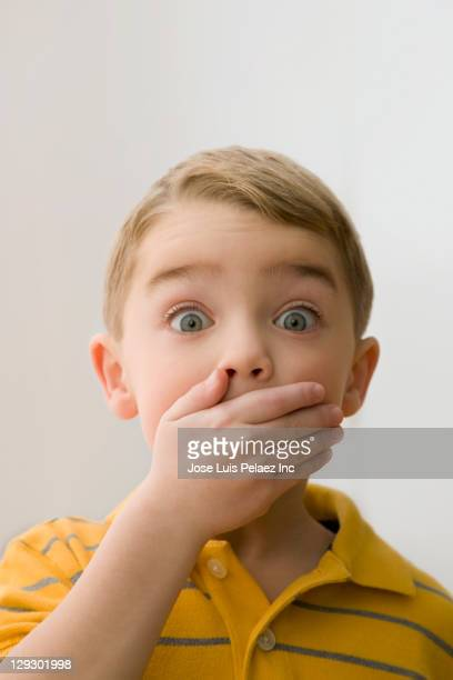 Surprised Caucasian boy covering mouth