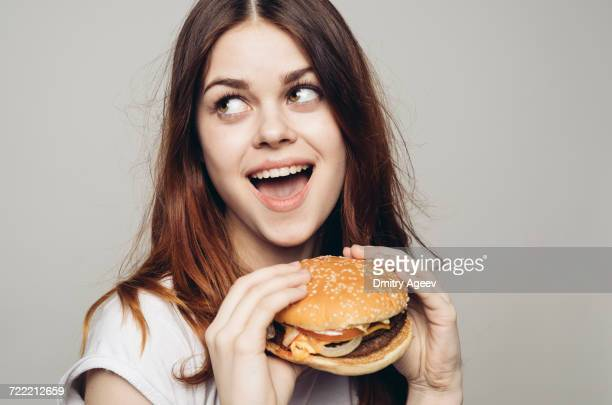 surprised caucasian woman holding cheeseburger - hongerig stockfoto's en -beelden