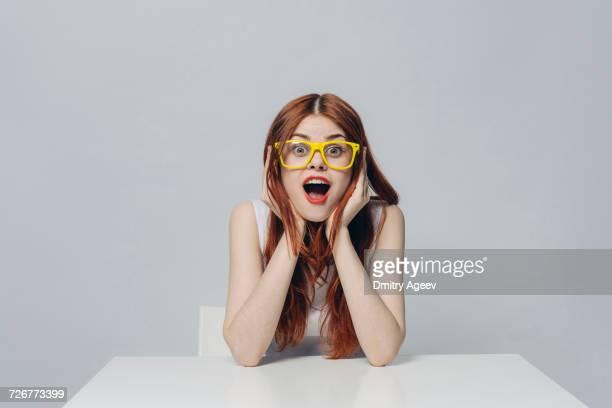 surprised caucasian woman sitting at table wearing yellow eyeglasses - surpresa - fotografias e filmes do acervo
