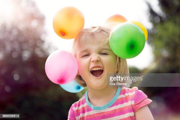 Surprised child with multi colored balloons stuck on her head