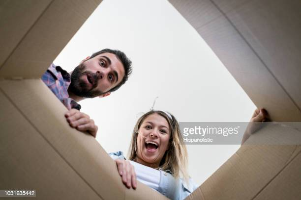 surprised couple opening a box while moving into their new place - hispanolistic stock photos and pictures