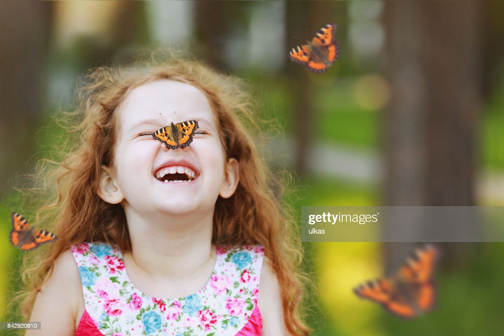 Surprised curly girl with a butterfly on his nose. : Stock Photo