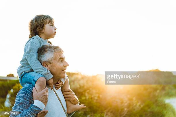 surprised father carrying son on shoulders - piggyback stock pictures, royalty-free photos & images