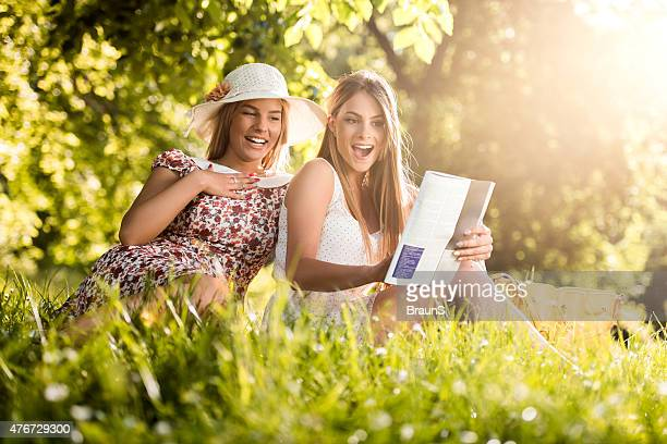 surprised female friends reading a magazine at the park. - nature magazine stock pictures, royalty-free photos & images