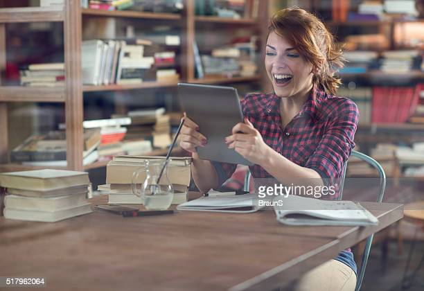 Surprised female student using digital tablet in the library.