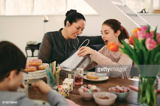 surprised girl looking at bag while sitting with mother during meal in birthday party - happy birthday images for sister stock pictures, royalty-free photos & images