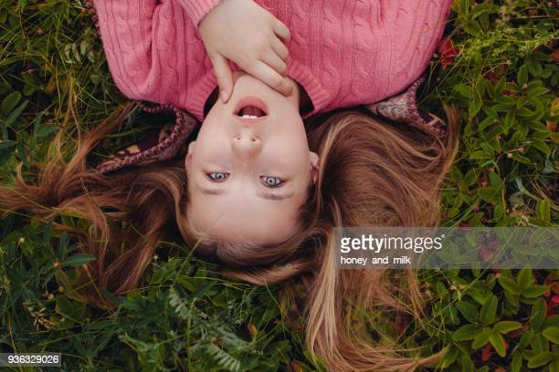 Surprised girl lying on grass with her hair spread out