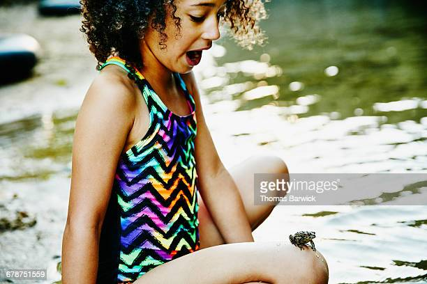 Surprised girl with frog perched on her knee