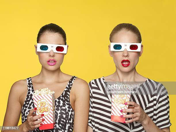 surprised girls watching 3D film with popcorn