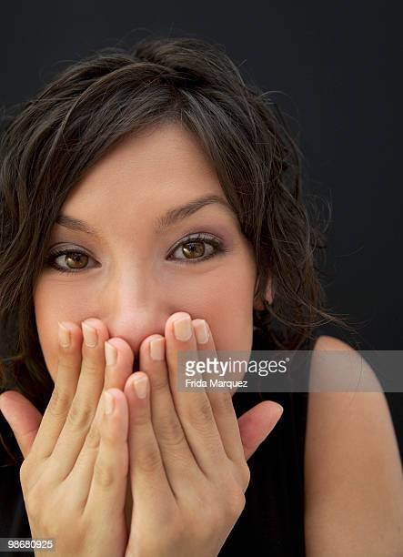 Surprised Hispanic woman with hands covering face