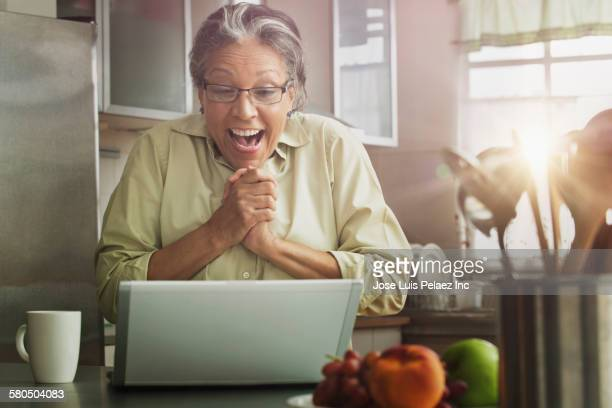 Surprised Hispanic woman with laptop in kitchen