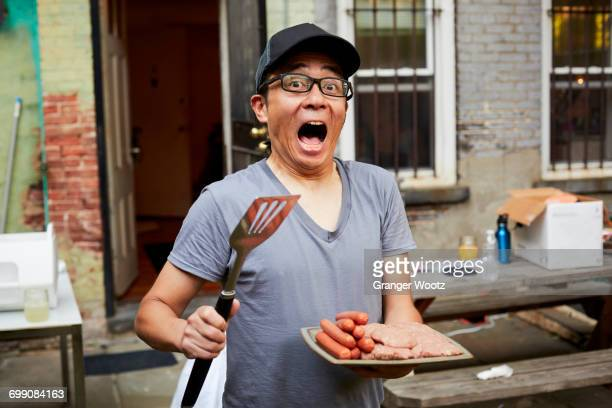 Surprised Japanese man holding plate of raw meat in backyard