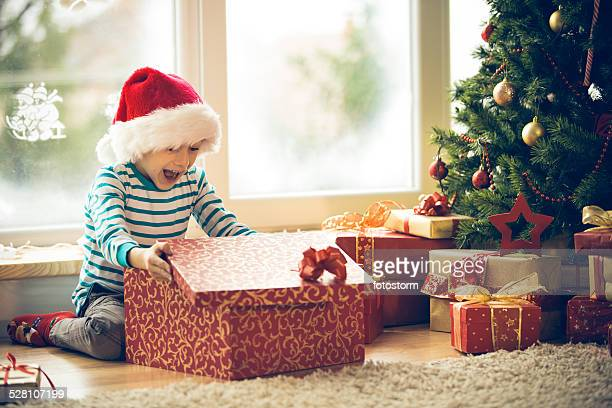 surprised little boy opening christmas present - openmaken stockfoto's en -beelden