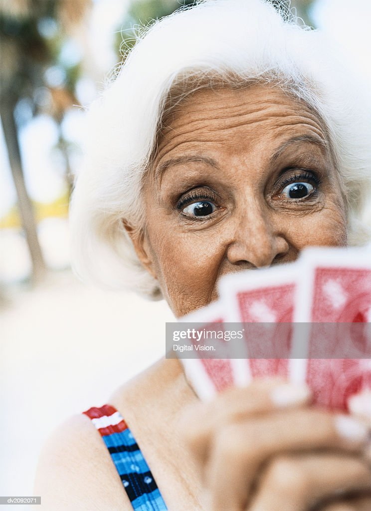 Surprised Looking Woman Looking Down at Her Cards : Stock Photo