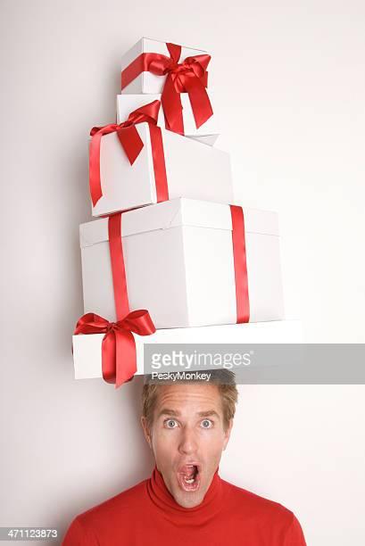 Überrascht Mann bringt Geschenke auf seinen Kopf weiße Wand