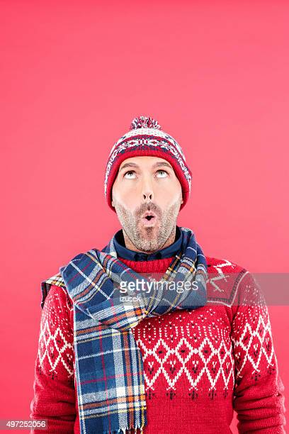 Surprised man in winter outfit against red background