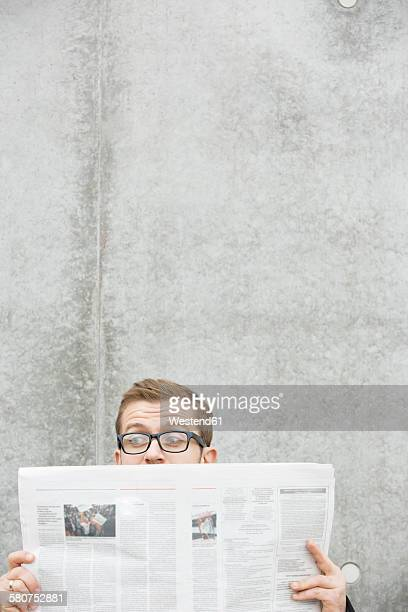 Surprised man reading newspaper at concrete wall