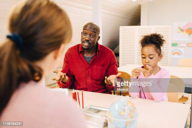 Surprised man sitting with son talking to teacher at classroom