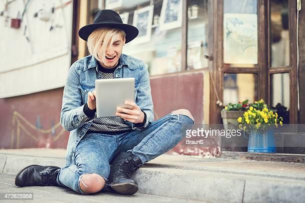 Sorprendido hombre usando tableta digital mientras se distiende en la calle.