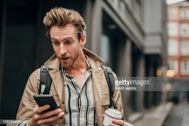 surprised man using phone on the street in city - surprise stock pictures, royalty-free photos & images