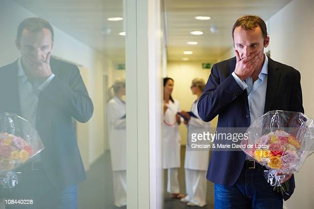 surprised man with flowers at hospital - david ramos fotografías e imágenes de stock