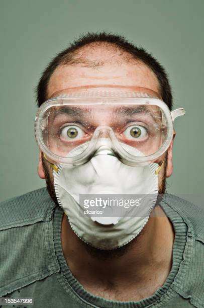Surprised man with workwear eye protection and mask