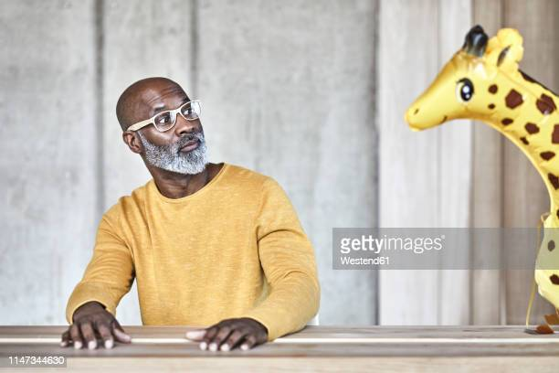 surprised mature businessman sitting at desk in office looking at giraffe figurine - out of context stock pictures, royalty-free photos & images
