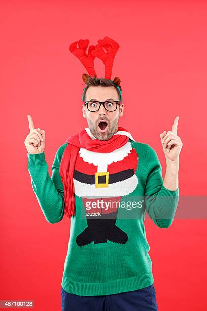 Surprised nerd man in funny winter outfit against red background