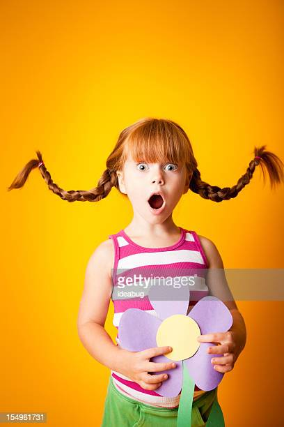 Surprised, Red-Haired Girl with Upward Braids and Oversized Flower