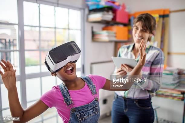 Surprised schoolgirl wearing VR headset by teacher