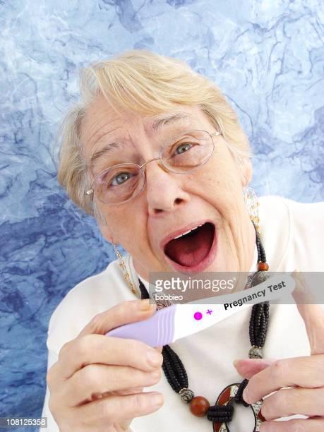 Surprised Senior Woman Holding Up Postive Pregnancy Test
