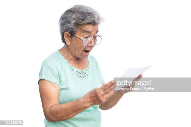 surprised senior woman looking at paper against white background - alleen één seniore vrouw stockfoto's en -beelden