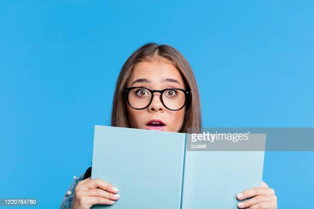 surprised teenage girl peeking over blue book - girls stock pictures, royalty-free photos & images