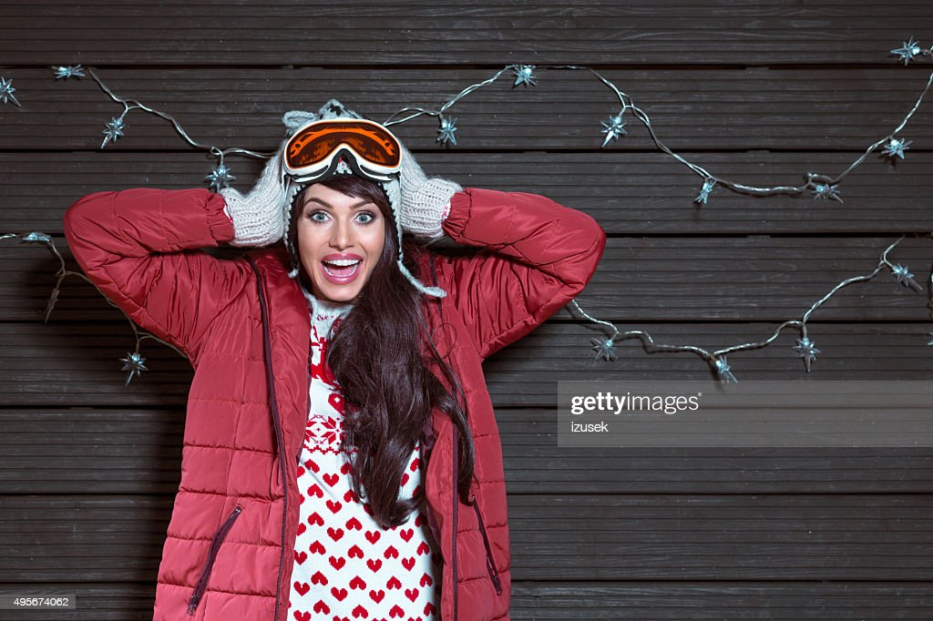 Surprised woman in winter outfit, wearing puffer jacket and goggle : Stock Photo