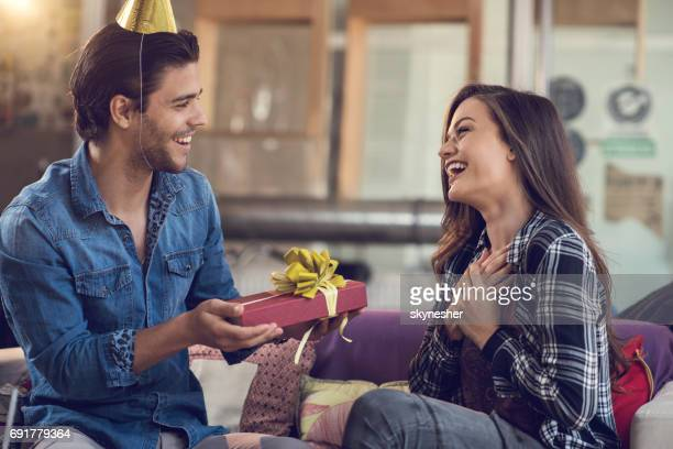 surprised woman receiving birthday present from her boyfriend. - birthday gift stock pictures, royalty-free photos & images
