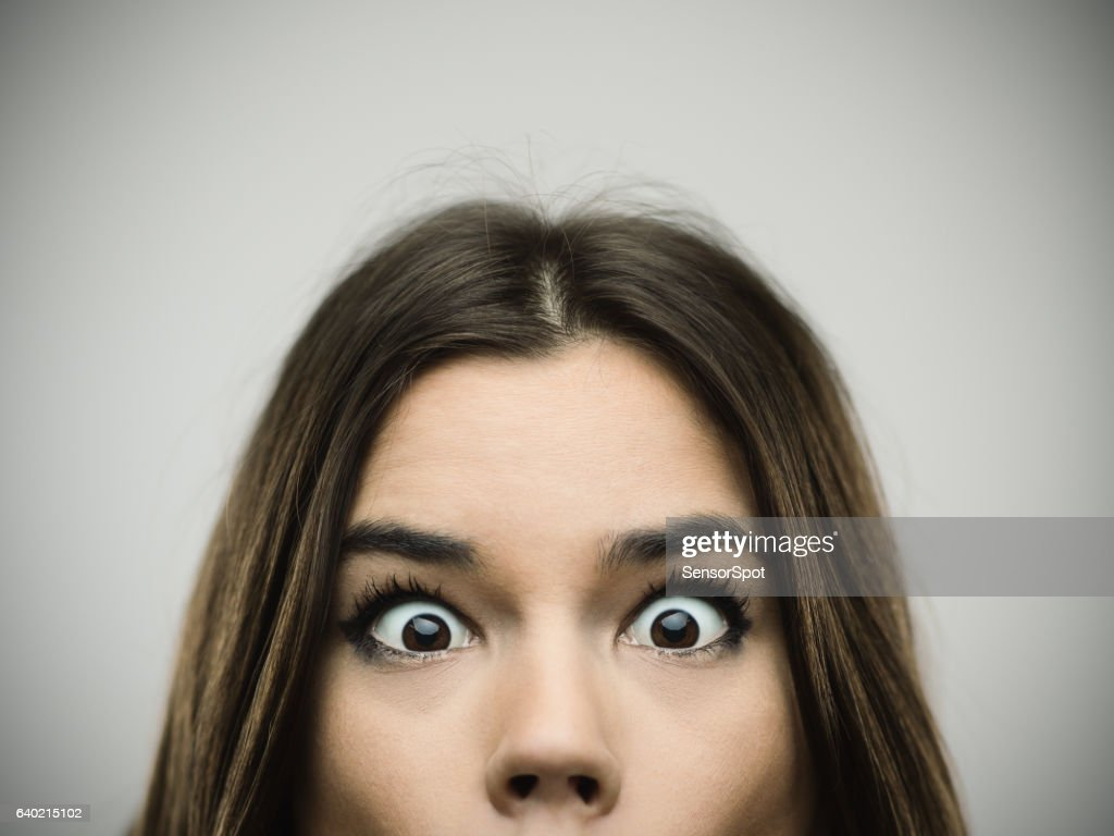 Surprised woman smiling against gray background : Stock Photo