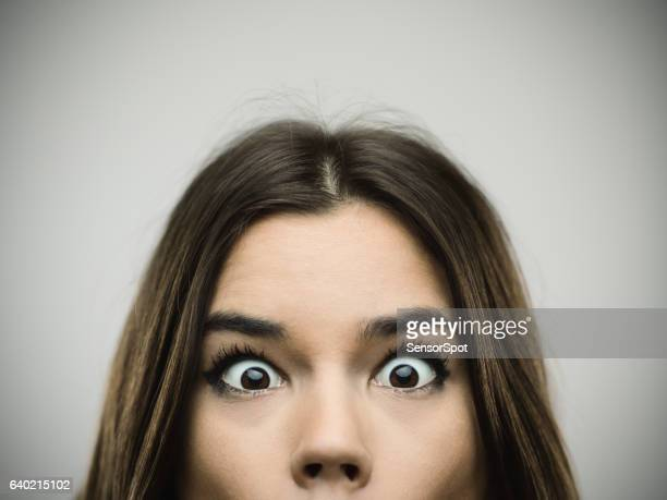 Surprised woman smiling against gray background