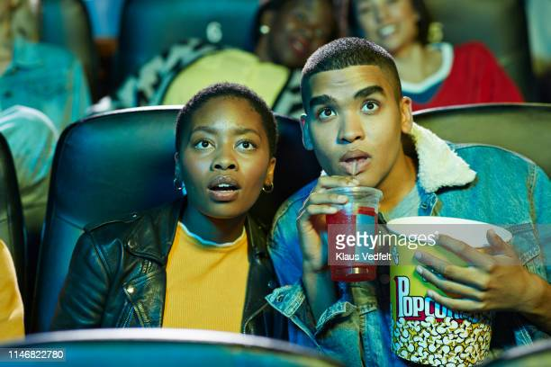 surprised young man drinking soda while watching movie with friend in cinema hall - industria cinematografica foto e immagini stock