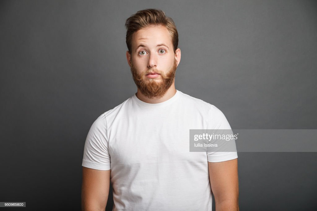 Surprised young man posing on gray : Stock Photo