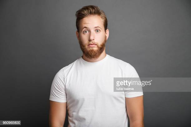 Surprised young man posing on gray