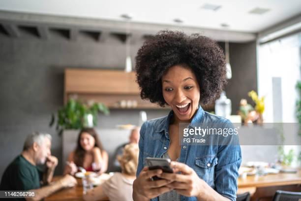 mulher nova surpreendida que prende um telemóvel - ciência e tecnologia - fotografias e filmes do acervo