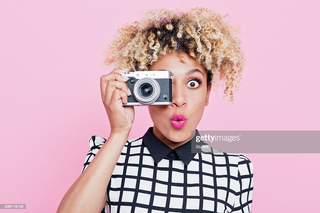 Surprised young woman wearing sunglasses, holding camera : Stock Photo
